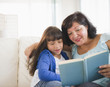 Hispanic mother and daughter reading a book
