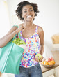 Black woman carrying reusable grocery bag