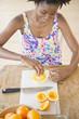 Black woman squeezing fresh orange juice