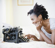 Black woman using old-fashioned typewriter