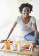 Black woman having breakfast in bed