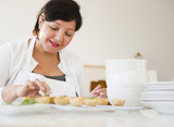 Smiling Hispanic woman baking