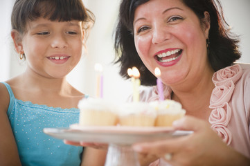 Hispanic mother and daughter holding cupcakes