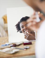 Smiling Black woman putting on lipstick