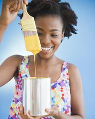 Black woman holding paintbrush dripping paint