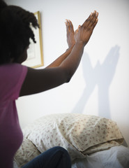 Black woman making hand shadows on wall