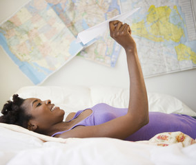 Black woman laying in bed holding paper airplane