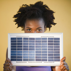 Black woman holding solar panel