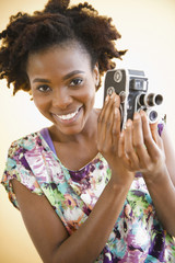 Black woman holding old-fashioned video camera
