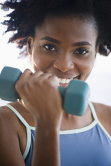 Black woman exercising with hand weights