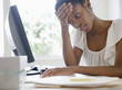 Frustrated Black businesswoman working at desk