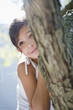 Hispanic girl hiding behind tree