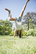 Hispanic girl doing cartwheels in grass