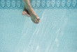 Caucasian woman's feet underwater in swimming pool