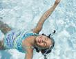Hispanic girl floating in swimming pool