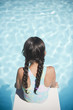 Hispanic girl sitting on diving board over swimming pool