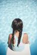 Hispanic girl sitting on diving board over swimming pool