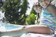 Hispanic girls sitting on edge of swimming pool