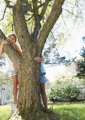 Hispanic children playing near tree