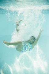 Hispanic girl jumping into swimming pool