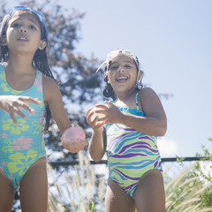 Hispanic girls in bathing suits playing with water balloons