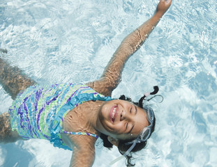 Hispanic girl floating in swimming pool
