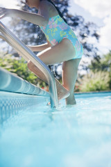 Hispanic girl climbing ladder in swimming pool