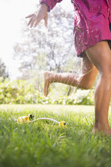 Hispanic girl running through sprinkler