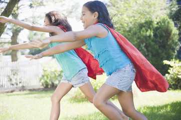 Hispanic girls in capes playing superheroes