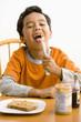 Hispanic boy making peanut butter and jelly sandwich