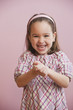 Grinning Caucasian girl with hands clasped