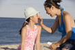 Mother putting sunscreen on daughter at beach