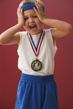 Frustrated Caucasian boy wearing sports medal