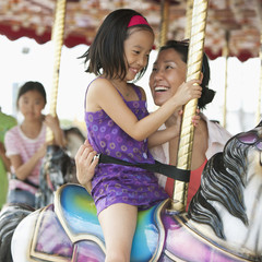 Mother and daughter riding carousel