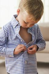Caucasian boy buttoning his shirt