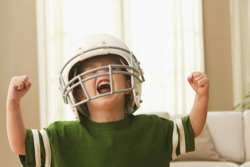 Cheering Caucasian boy in football uniform