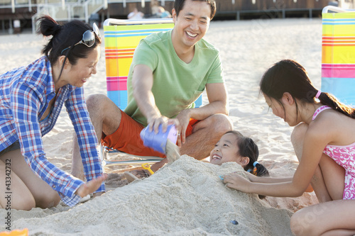 Family burying daughter on beach