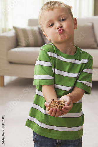 Caucasian boy holding handful of peanuts