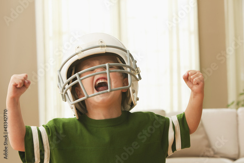 Cheering Caucasian boy in football uniform