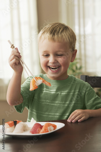Smiling Caucasian boy eating sushi