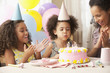 Mixed race family watching girl blow out birthday candles