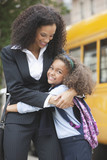 Mixed race mother hugging daughter near school bus