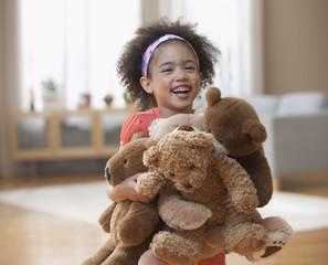 Mixed race girl holding teddy bears