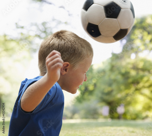 Caucasian boy heading soccer ball