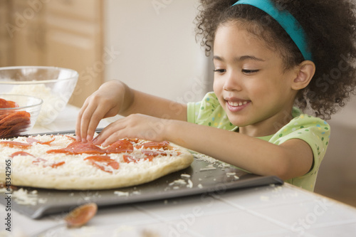 Mixed race girl making pizza