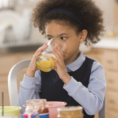 Mixed race girl drinking orange juice