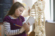 Caucasian girl studying skeleton in classroom