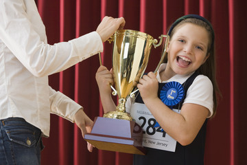 Caucasian girl standing on stage wearing competition number and receiving trophy