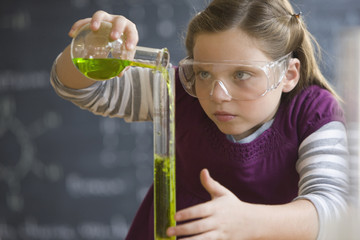 Caucasian girl doing chemistry experiment in classroom