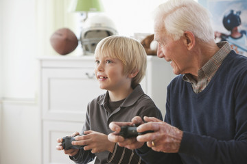 Caucasian man playing video game with grandson